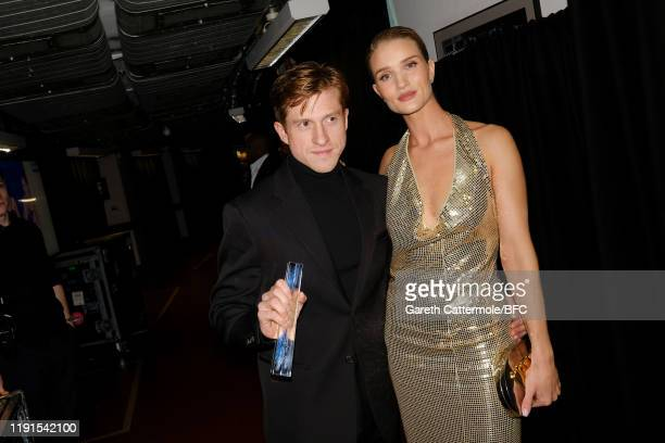 Daniel Lee poses with Rosie Huntington-Whiteley backstage after accepting the Accessories Designer of the Year award on behalf of Bottega Veneta...