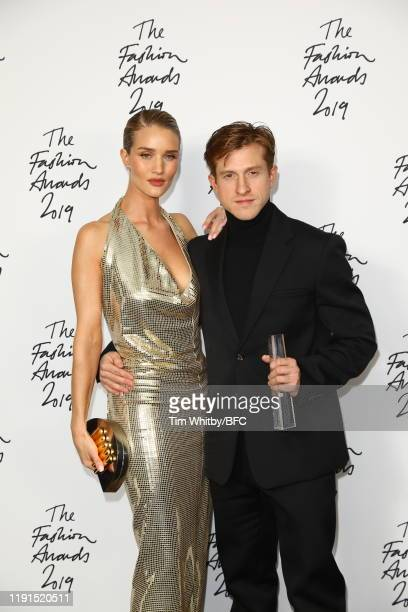 Daniel Lee poses with Rosie Huntington-Whiteley in the winners room after accepting the Accessories Designer of the Year award on behalf of Bottega...