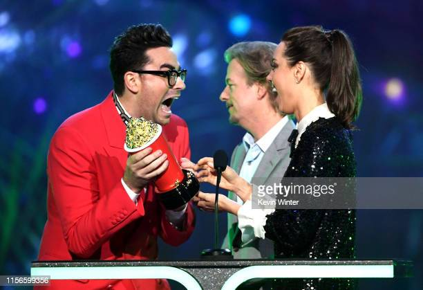 Daniel Levy accepts the Best Comedic Performance award for 'Schitt's Creek' onstage from David Spade and Aubrey Plaza during the 2019 MTV Movie and...