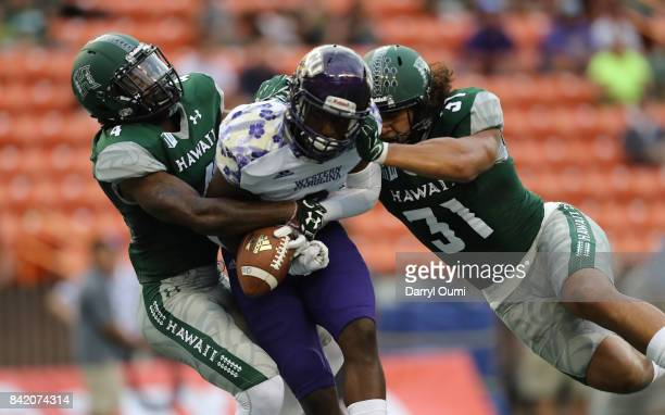 Daniel Lewis Jr of the Hawaii Rainbow Warriors and Jahlani Tavai break up a pass intended for Connell Young of the Western Carolina Catamounts in the...