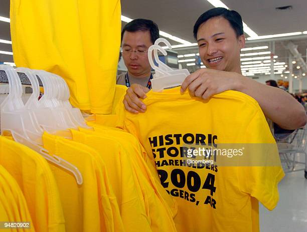 Daniel Li left and Thomas Chui WalMart employees from China in town for the upcoming shareholders meeting look over tee shirts at the original...