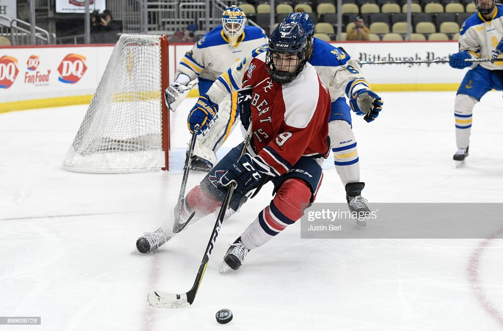 Daniel Mantenuto #9 of the Robert Morris Colonials controls the puck as Lukas Kaelble #6 of the Lake Superior Lakers defends in the second period during the game at PPG PAINTS Arena on December 29, 2017 in Pittsburgh, Pennsylvania.