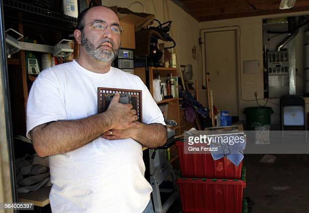Daniel Martinez of Highland clutches a picture of his wife Maureen Martinez at his home after San Bernardino County Sheriff's Search and Rescue team...