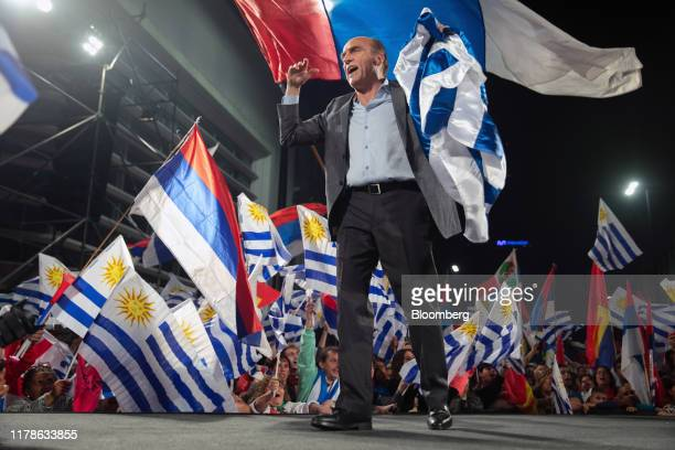Daniel Martinez presidential candidate for the Broad Front party greets attendees while holding a Uruguay flag at the party's headquarters during an...