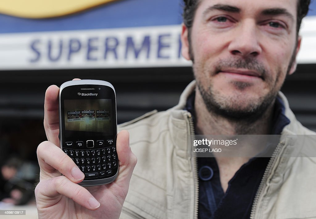 Daniel Martinez shows a picture of his three winning tickets on his mobile phone in Llica d'Amunt, near Barcelona, on December 31, 2013. The Spanish region of Catalonia, where leaders are pushing for independence from Spain, awarded millions of euros today in its first New Year lottery, defying the country's national prize draw. The new lottery was dubbed 'La Grossa' in Catalan, a nod to 'El Gordo', or 'The Fat One', the top prize in Spain's traditional Christmas draw which saw its sales fall this year despite its popularity.