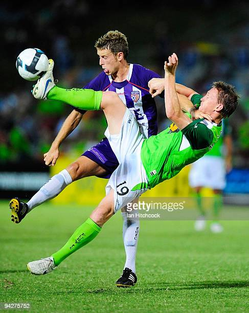 Daniel McBreen of the Fury and Jamie Coyne of the Glory run after the ball during the round 18 match between the North Queensland Fury and the Perth...
