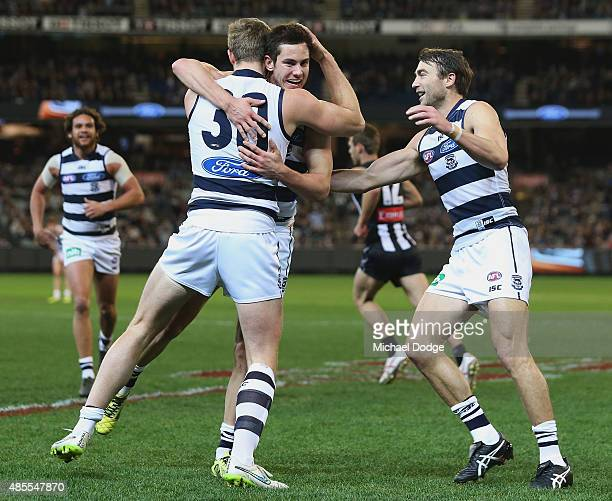 Daniel Menzel of the Cats celebrates a goal with Nathan Vardy and Corey Enright during the round 22 AFL match between the Geelong Cats and the...