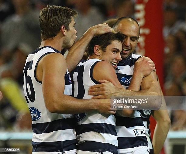 Daniel Menzel of the Cats celebrates his goal with Tom Hawkins and James Podsiadly during the round 24 AFL match between the Collingwood Magpies and...