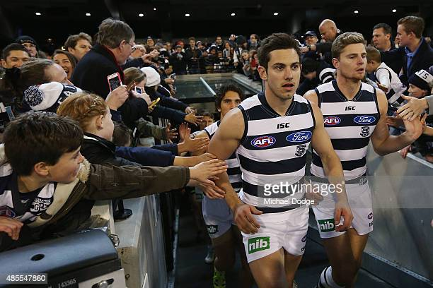 Daniel Menzel of the Cats runs out with Nathan Vardy for his first game since four knee reconstructions during the round 22 AFL match between the...