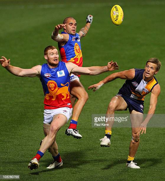 Daniel Merrett and Ashley McGrath of the Lions contest the ball against Mark LeCras of the Eagles during the round 19 AFL match between the West...