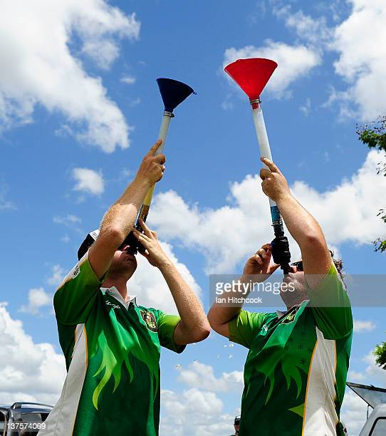 Daniel Mill and Dempsey McCoy from the team 'Wolf Pack' consume beer bongs at the end of their game during the 2012 Goldfield Ashes cricket...