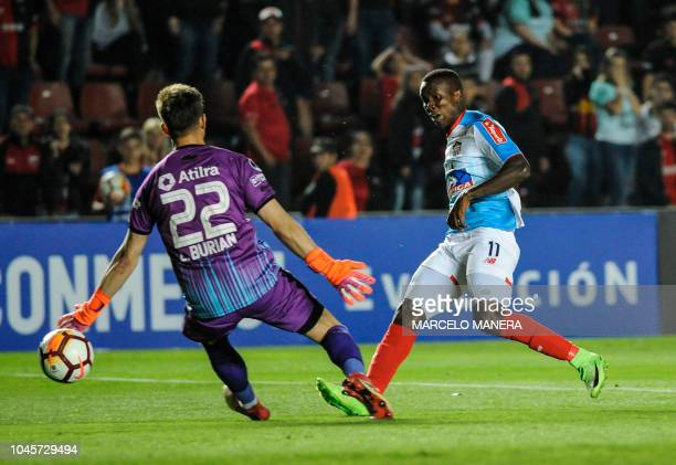 Daniel Moreno of Colombia's Junior scores past Argentina's Colon goalkeeper Leonardo Burian during their Copa Sudamericana 2018 football match at...