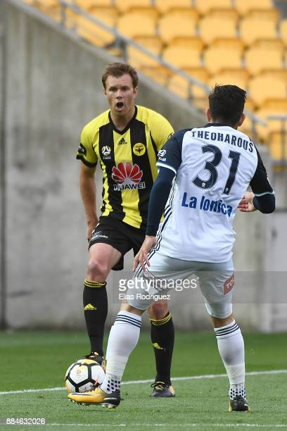 Daniel Mullen of the Wellington Phoenix looks to get past Christian Theoharous of Melbourne Victory during the round nine ALeague match between the...