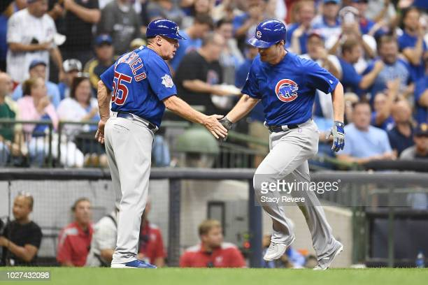Daniel Murphy of the Chicago Cubs is congratulated by third base coach Brian Butterfield following a solo home run against the Milwaukee Brewers...