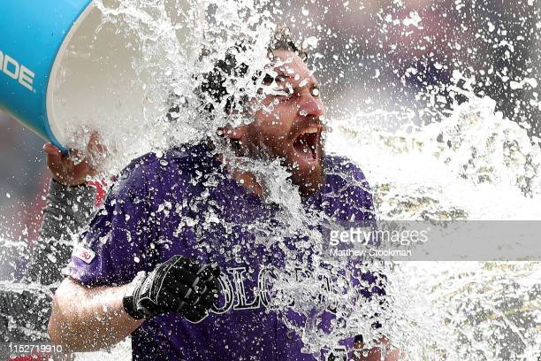 Daniel Murphy of the Colorado Rockies is doused with water by Tony Wolters after hitting a RBI walk off single in the tenth inning against the...