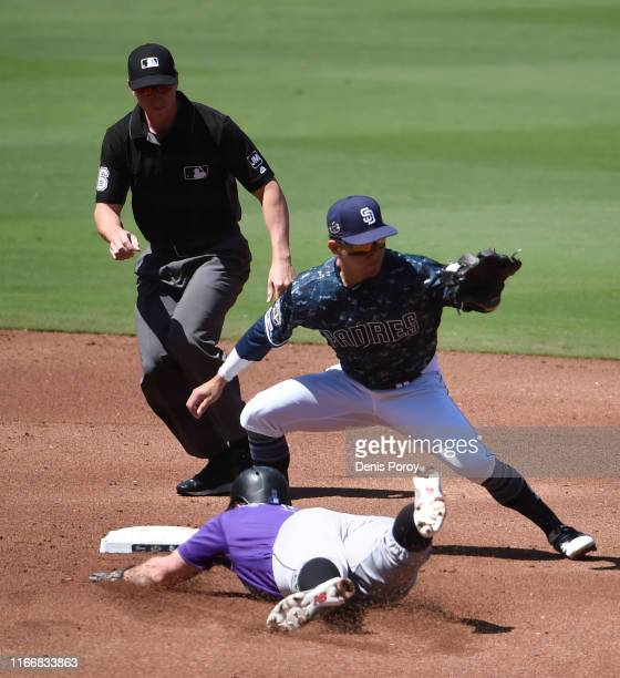 Daniel Murphy of the Colorado Rockies is tagged out by Luis Urias of the San Diego Padres as he slides into second base during the second inning of a...