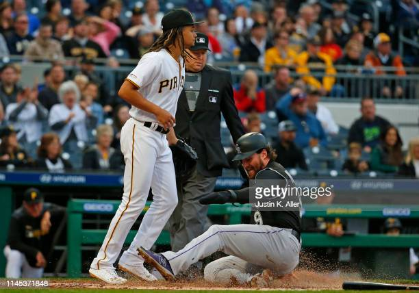 Daniel Murphy of the Colorado Rockies scores on a throwing error in the second inning against the Pittsburgh Pirates at PNC Park on May 21, 2019 in...