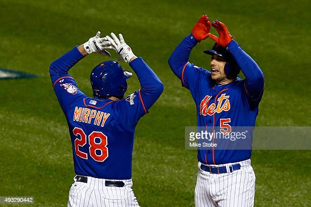 Daniel Murphy of the New York Mets celebrates with David Wright after hitting a two run home run in the first inning against Jake Arrieta of the...