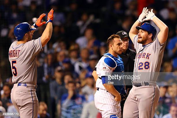 Daniel Murphy of the New York Mets celebrates with David Wright after hitting a two run home run in the eighth inning against the Chicago Cubs during...