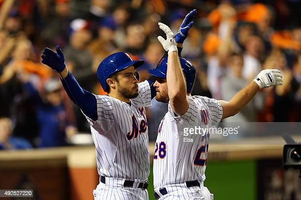 Daniel Murphy of the New York Mets celebrates with teammate Travis d'Arnaud after hitting a solo home run in the fourth inning against Clayton...
