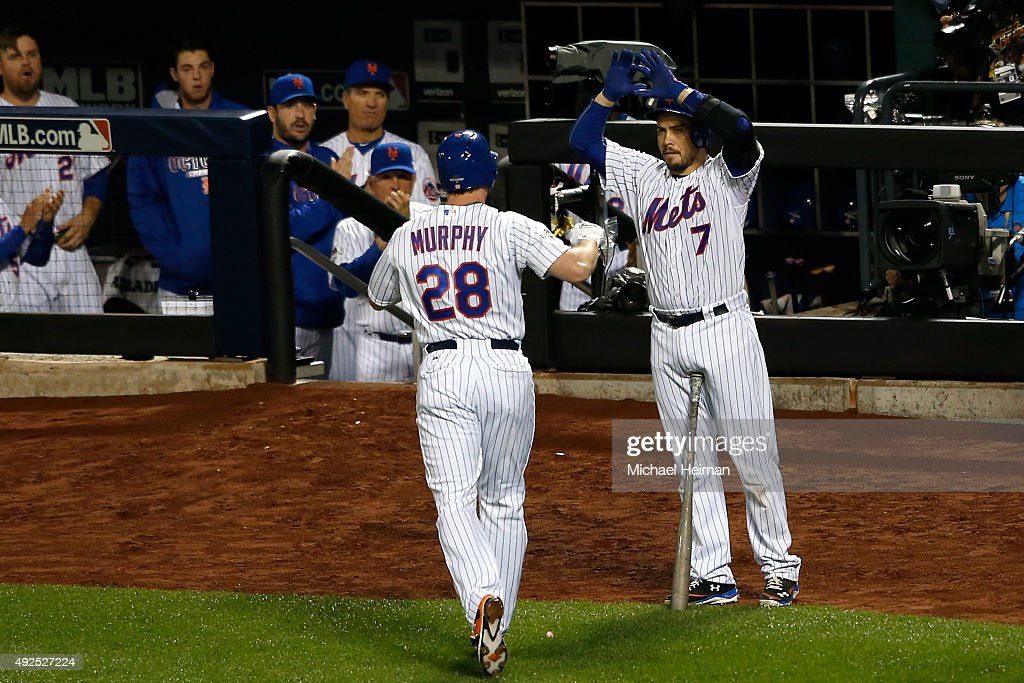 Daniel Murphy #28 of the New York Mets celebrates with teammate Travis d'Arnaud #7 after hitting a solo home run in the fourth inning against Clayton Kershaw #22 of the Los Angeles Dodgers during game four of the National League Division Series at Citi Field on October 13, 2015 in New York City.