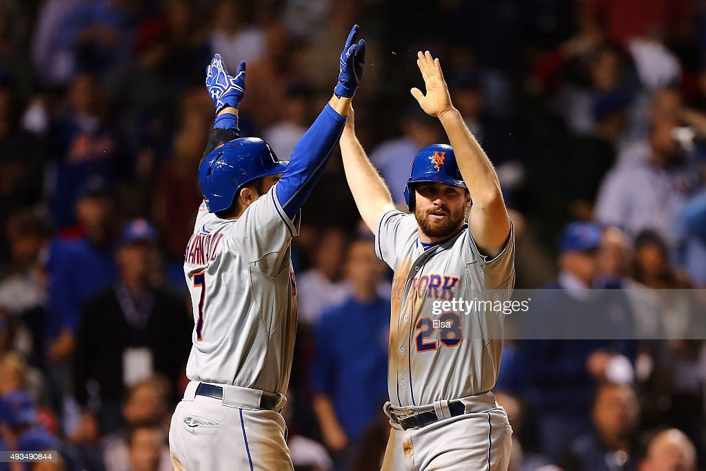 Daniel Murphy #28 of the New York Mets celebrates with Travis d'Arnaud #7 after scoring off of an RBI ground out hit by Lucas Duda #21 in the seventh inning against Justin Grimm #52 of the Chicago Cubs during game three of the 2015 MLB National League Championship Series at Wrigley Field on October 20, 2015 in Chicago, Illinois.