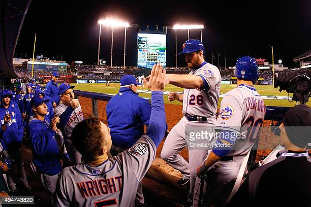 Daniel Murphy of the New York Mets is greeted by David Wright of the New York Mets in the dugout after scoring a run on an RBI single hit by Lucas...
