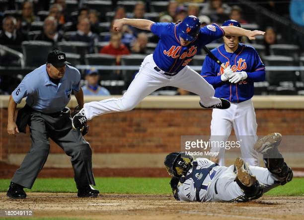 Daniel Murphy of the New York Mets jumps over Martin Maldonado of the Milwaukee Brewers in an attempt to score during the sixth inning on September...