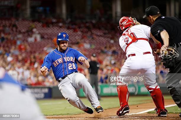 Daniel Murphy of the New York Mets slides at home plate to score a run after a double by Lucas Duda in the third inning against the Cincinnati Reds...