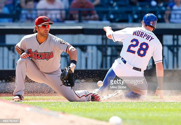 Daniel Murphy of the New York Mets slides in safely ahead of the tag from Eric Chavez of the Arizona Diamondbacks during game one of a doubleheader...