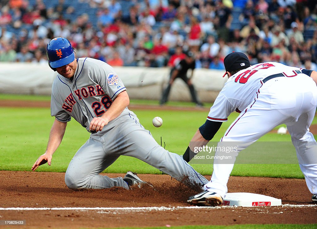 Daniel Murphy #28 of the New York Mets slides safely into third base during game two of a doubleheader against Chris Johnson #23 of the Atlanta Braves at Turner Field on June 18, 2013 in Atlanta, Georgia.