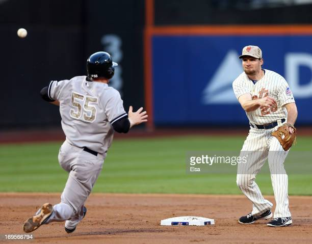 Daniel Murphy of the New York Mets turns the double play to end the inning as Lyle Overbay of the New York Yankees is out at second base in the...