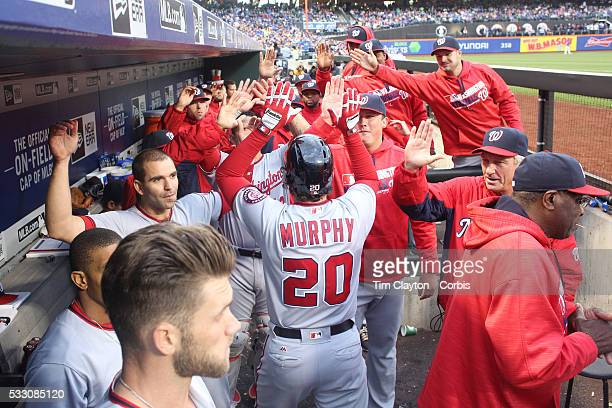 Daniel Murphy of the Washington Nationals celebrates with team mates as he returns to the dugout after hitting a two run home run off Matt Harvey of...