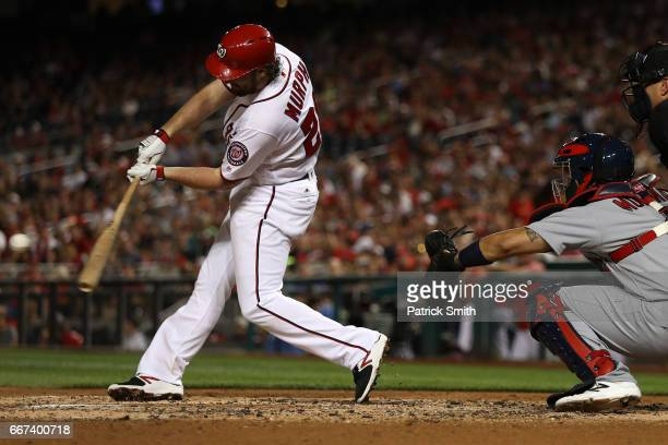 Daniel Murphy of the Washington Nationals hits an hits an RBI single that scores two runs against the St Louis Cardinals during the third inning at...