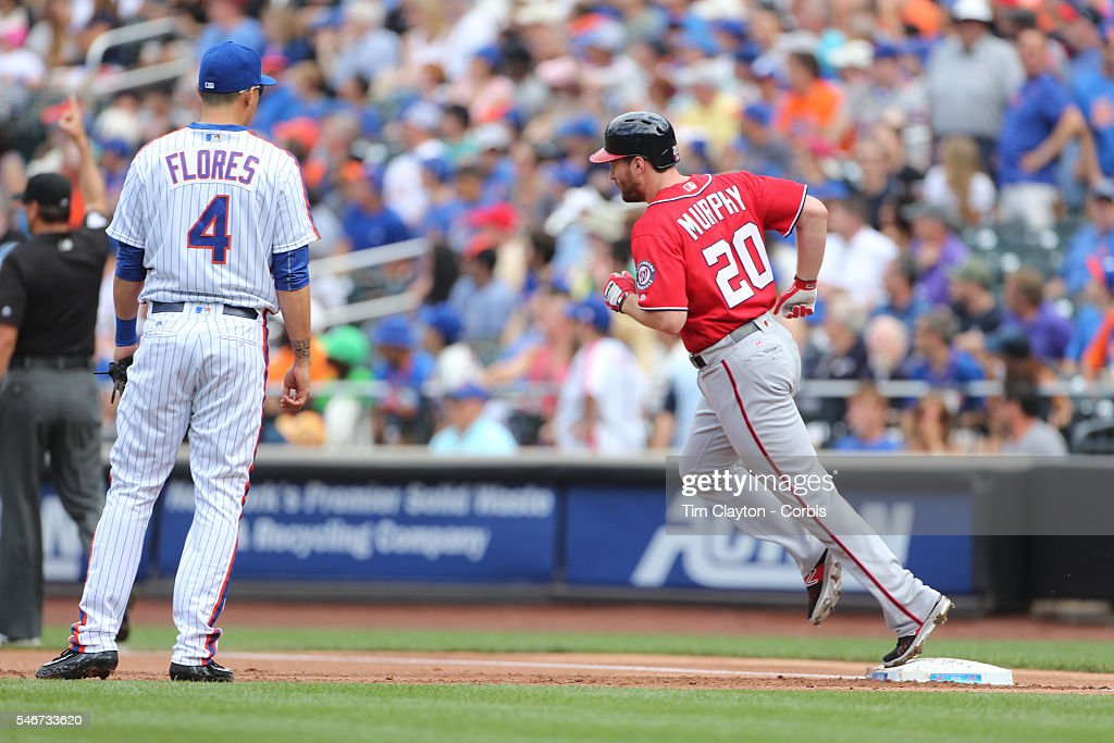 Daniel Murphy #20 of the Washington Nationals runs the bases after hitting a two run home run in the first inning watched by Wilmer Flores #4 of the New York Mets during the Washington Nationals Vs New York Mets regular season MLB game at Citi Field on July 10, 2016 in New York City.
