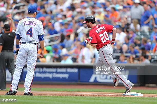Daniel Murphy of the Washington Nationals runs the bases after hitting a two run home run in the first inning watched by Wilmer Flores of the New...