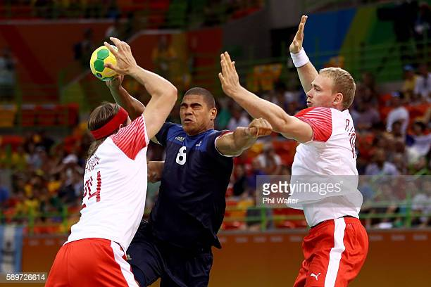 Daniel Narcisse of France is blocked by Mikkel Hansen and Rene Hansen of Denmark during the Men's Preliminary Group A match between France and...
