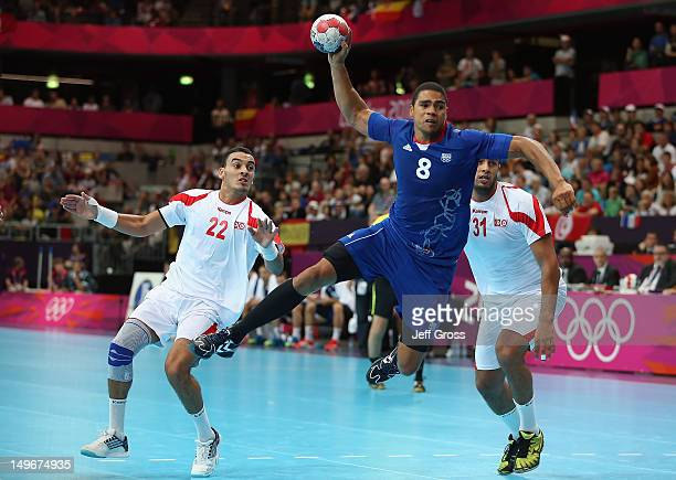 Daniel Narcisse of France shoots and scores between Oussama Boughanmi and Marouan Chouiref of Tunisia in the Men's Preliminaries Group A match...