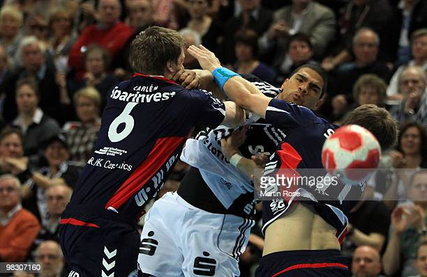 Daniel Narcisse of Kiel challenges Lasse Hansen and Oscar Carlen of FlensburgHandewitt for the ball during the Toyota Handball Bundesliga match...