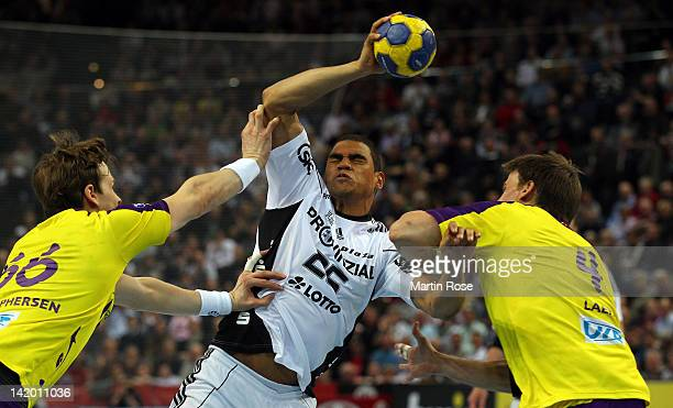 Daniel Narcisse of Kiel is challenged by Sven Christophersen and Torsten Laen of Berlin during the Toyota Handball Bundesliga match between THW Kiel...