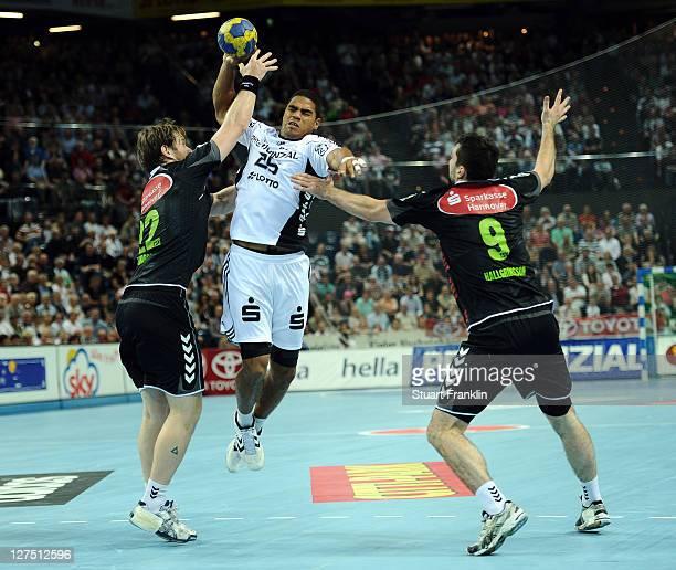 Daniel Narcisse of Kiel is challenged by Vigir Svavarsson and Asgeir Orn Hallgrimsson of Hannover during the Toyota handball Bundesliga match between...