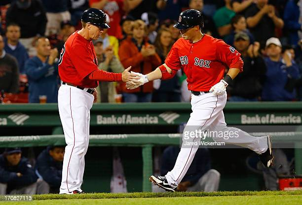 Daniel Nava is congratulated by third base coach Brian Butterfield of the Boston Red Sox after hitting a solo home run in the second inning against...