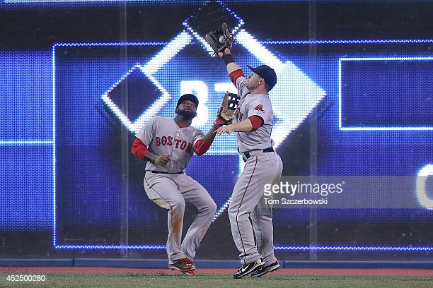 Daniel Nava of the Boston Red Sox catches a fly ball avoiding a collision with Jackie Bradley Jr #25 in the seventh inning during MLB game action...