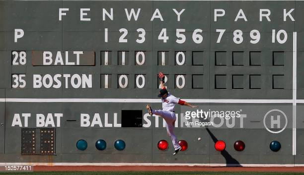 Daniel Nava of the Boston Red Sox is unable to catch a ball hit by Manny Machado of the Baltimore Orioles in the sixth inning at Fenway Park on...