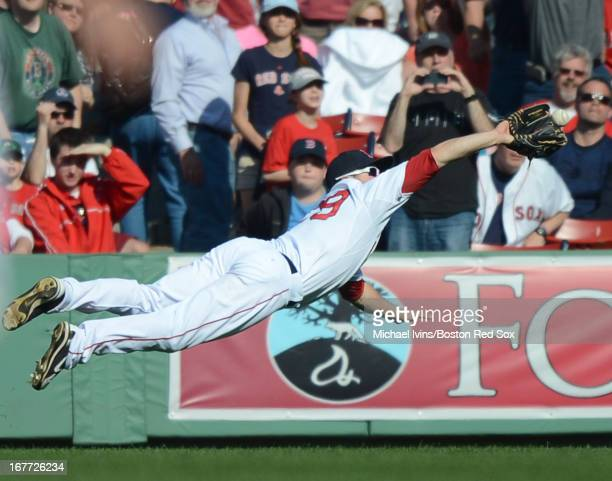 Daniel Nava of the Boston Red Sox makes a diving catch against the Houston Astros in the ninth inning on April 28 2013 at Fenway Park in Boston...