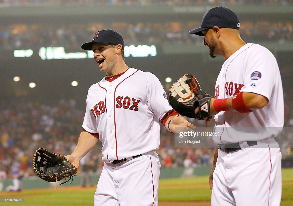 Daniel Nava #29 of the Boston Red Sox reacts with Shane Victorino #18 after making a key defensive play in the 8th inning against the Toronto Blue Jays at Fenway Park on June 27, 2013 in Boston, Massachusetts.