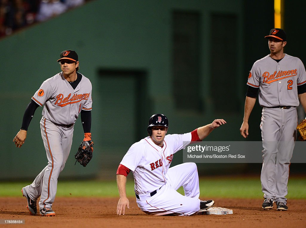 Daniel Nava #29 of the Boston Red Sox watches as Jonny Gomes #5 is called out after a double play by J.J. Hardy #2 and Brian Roberts #1 of the Baltimore Orioles stopped a potential rally in the ninth inning on August 29, 2013 at Fenway Park in Boston Massachusetts. The Orioles held on to win 3-2.