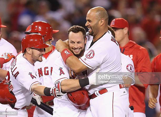 Daniel Nava of the Los Angeles Angels of Anaheim is mobbed by Albert Pujols Johnny Giavotella and other teammates after his ground ball led to a...