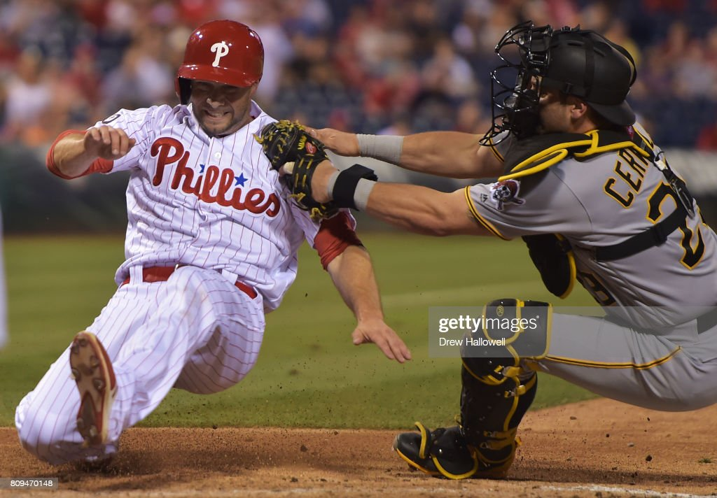 Daniel Nava #25 of the Philadelphia Phillies gets tagged out at home plate by Francisco Cervelli #29 of the Pittsburgh Pirates in the seventh inning at Citizens Bank Park on July 5, 2017 in Philadelphia, Pennsylvania. The Pirates won 5-2.