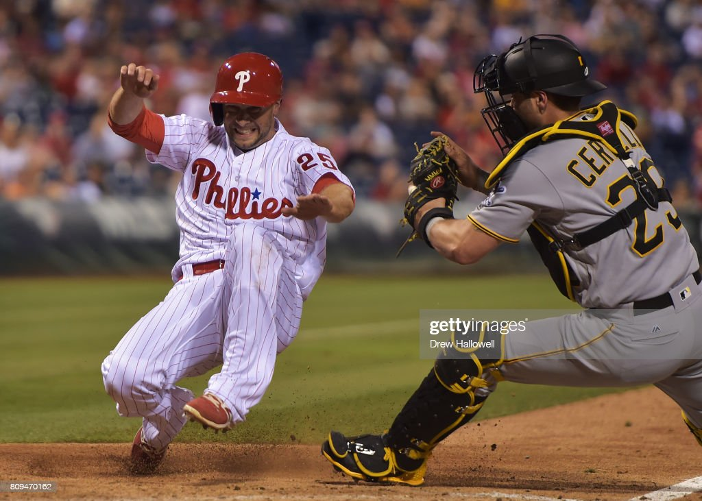 Daniel Nava #25 of the Philadelphia Phillies goes into his slide before getting tagged out at home plate by Francisco Cervelli #29 of the Pittsburgh Pirates in the seventh inning at Citizens Bank Park on July 5, 2017 in Philadelphia, Pennsylvania. The Pirates won 5-2.
